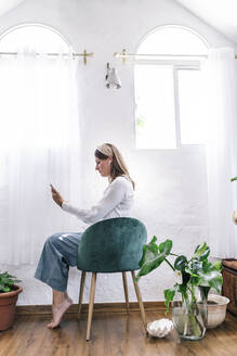 Woman using smart phone while sitting on chair in bedroom at home - ERRF03907