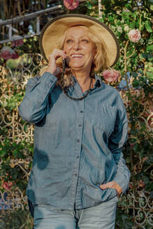 Portrait of happy senior woman on the phone in her garden - ERRF03944