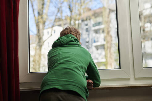 Boy looking out through window at home - MMIF00275