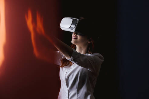 Young woman gesturing while using VR glasses over black background - LJF01536