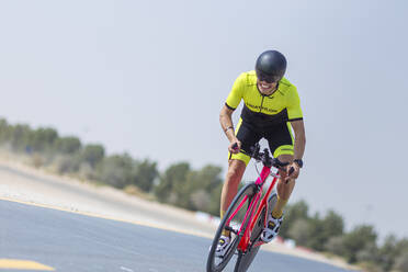 Determined cyclist riding bicycle on road against clear sky, Dubai, United Arab Emirates - SNF00238
