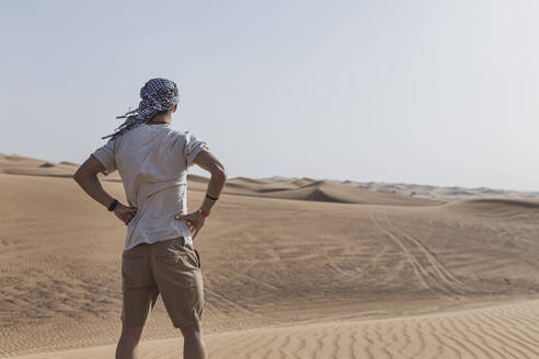 Young male tourist standing on sand dunes in desert at Dubai, United Arab Emirates - SNF00241