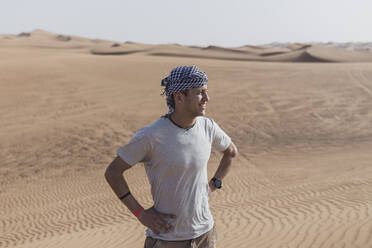 Male tourist looking away while standing on sand dunes in desert at Dubai, United Arab Emirates - SNF00244