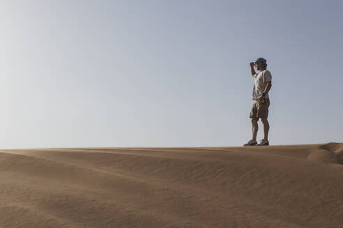 Male tourist shielding eyes while standing on sand dune against clear sky at Dubai, United Arab Emirates - SNF00247