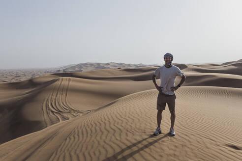 Happy male tourist standing on sand dunes in desert at Dubai, United Arab Emirates - SNF00250
