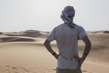 Male tourist standing on sand dunes in desert at Dubai, United Arab Emirates - SNF00253