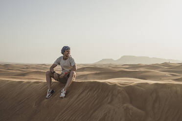 Male tourist looking away while sitting on sand dunes in desert at Dubai, United Arab Emirates - SNF00256