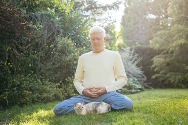Senior man meditating with cat in garden - AFVF06398