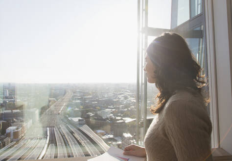 Thoughtful businesswoman at sunny window overlooking city - CAIF27529