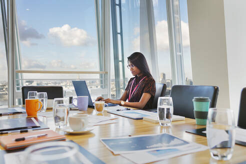 Focused businesswoman working at laptop in conference room - CAIF27553
