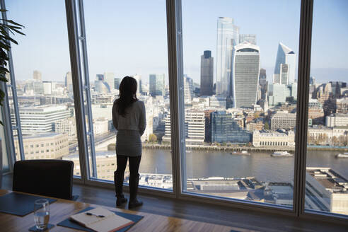 Thoughtful businesswoman looking at cityscape view, London, UK - CAIF27649