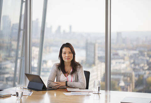 Portrait confident businesswoman working in urban conference room - CAIF27652