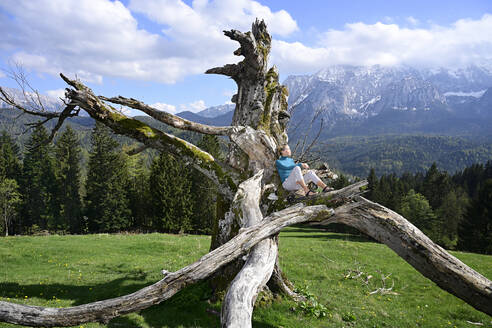 Woman relaxing on dead tree against mountains during sunny day - ECPF00951