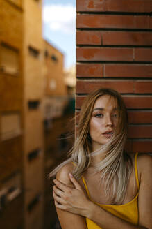 Beautiful woman with long blond hair standing against brick wall in balcony - TCEF00718