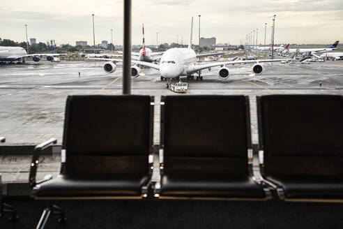 South Africa, Johannesburg, Airplane on tarmac seen from airport terminal with empty chairs in foreground - VEGF02336