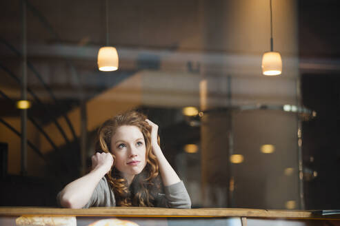 Thoughtful woman leaning on table seen through window in coffee shop - DIGF12472