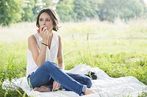 Beautiful young woman eating apple while sitting on picnic blanket at park - DIGF12481