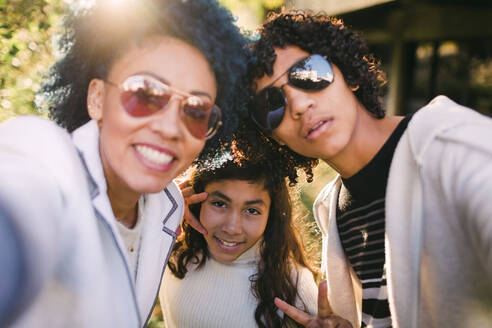 Mother and son wearing sunglasses while standing with girl in park - DCRF00202