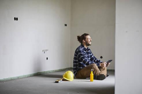 Happy worker on a construction site having a break sitting on the floor - MJFKF00231