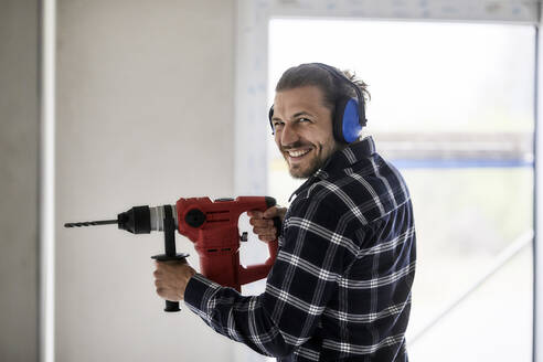 Portrait of smiling worker using electric drill on a construction site - MJFKF00234
