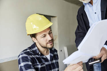 Architect and worker discussing building plan on a construction site - MJFKF00270