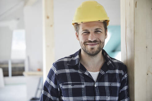 Portrait of a smilling worker wearing hard hat on a construction site - MJFKF00276