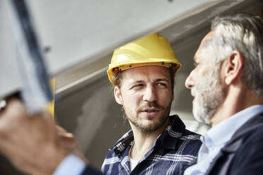 Architect and worker talking at the window on a construction site - MJFKF00282