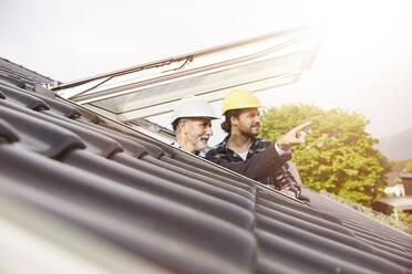 Two men wearing hard hats looking out of roof window - MJFKF00285