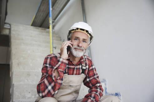 Construction worker phoning at construction site - MJFKF00300