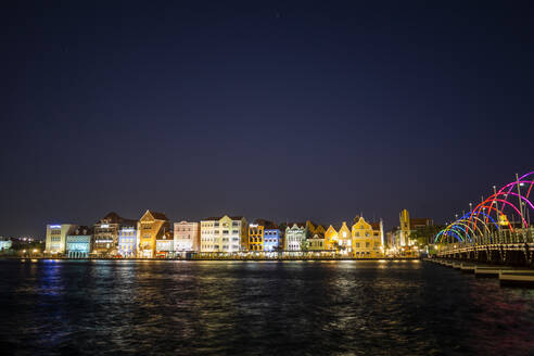 Illuminated buildings by sea against clear sky at night in Willemstad, Curacao - JLOF00413