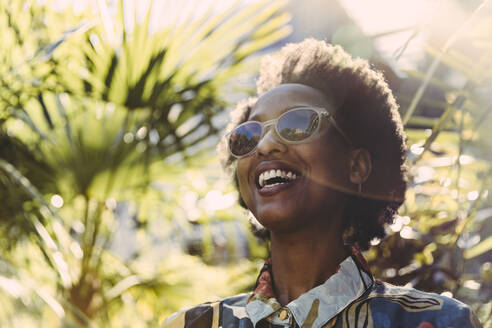 Portrait of happy young woman wearing sunglasses in garden - MFF05812