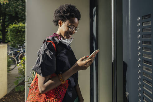 Smiling young woman with textile protective mask standing in front of entry door looking at smartphone - MFF05845