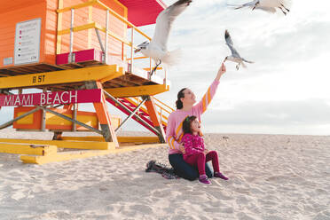Mother feeding seagulls while sitting with daughter at Miami beach, Florida, USA - GEMF03797