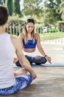 Yoga instructor practicing lotus position with man in gazebo at Ciutadella Park - JNDF00154