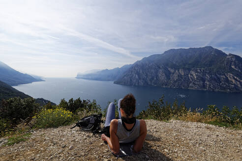 Italy, Trentino, Torbole, Rear view of woman looking at Lake Garda surrounded with mountains  - UMF00937