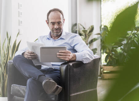 Portrait of smiling businessman with digital tablet and documents working at home - UUF20375