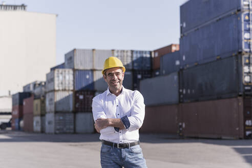 Portrait of confident businessman wearing safety helmet in front of cargo containers - UUF20411