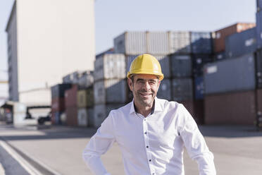 Portrait of smiling businessman wearing safety helmet in front of cargo containers - UUF20414