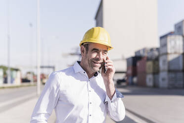 Portrait of smiling businessman on the phone at industrial site - UUF20420
