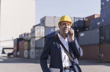 Portrait of businessman on the phone in front of cargo containers - UUF20423