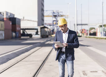 Businessman wearing safety helmet using digital tablet at industrial site - UUF20426