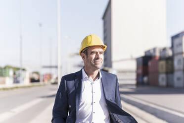 Portrait of businessman wearing safety helmet at industrial site - UUF20429