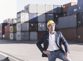 Portrait of relaxed businessman wearing safety helmet at industrial site - UUF20432