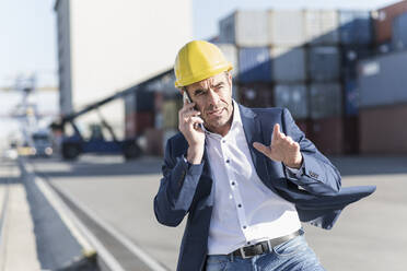 Portrait of businessman on the phone at industrial site - UUF20435