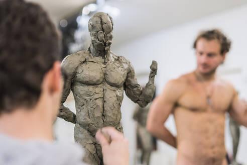 Student forming sculpture, naked model in the background - FBAF01557
