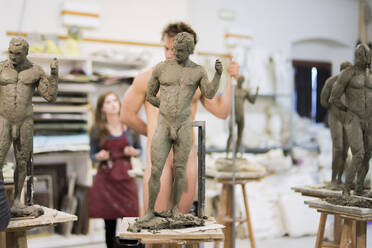Sculptures in the foreground, nude model in the background during class - FBAF01563