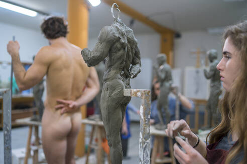 Female student working at sculpture, nude model in the background - FBAF01575