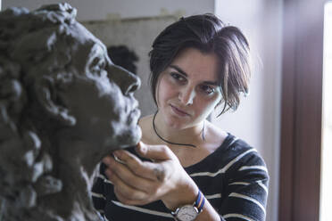 Female student looking at bust of woman - FBAF01581