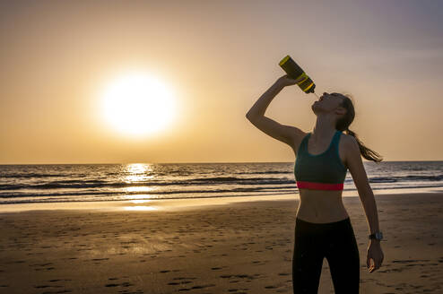 Sporty woman drinking water at the sea at sunset, Gran Canaria, Spain - DIGF12569