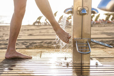 Man washing his feet at the beach - DIGF12572